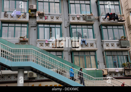 Chinese Pedestrians on steps outside apartment block Shanghai China - Stock Photo