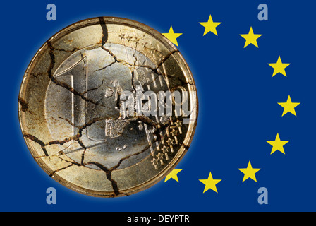 Euro coin in pieces and EU flag, symbolic image for debt crisis in Europe - Stock Photo