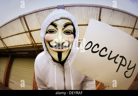 Man wearing the Guy Fawkes mask used by the Occupy movement holding a protest sign, protesting against the power - Stock Photo