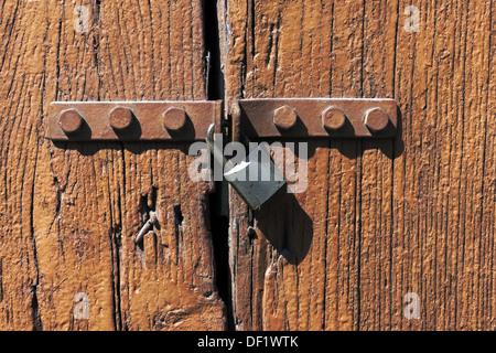 locked old wooden door with lock - Stock Photo