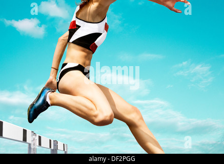 Female hurdle runner leaping over the hurdle - Stock Photo