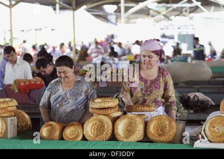 Two local women selling traditional bread on Chorsu Bazaar, Tashkent, Uzbekistan, Central Asia - Stock Photo