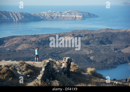 SANTORINI (THIRA), CYCLADES, GREECE. A holidaymaker photographing the view from the cliff-top village of Imerovighli - Stock Photo