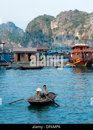 A Vietnamese man and woman in a rowboat near a floating village off Cat Ba Island in Lan Ha Bay, Halong Bay, Vietnam. - Stock Photo