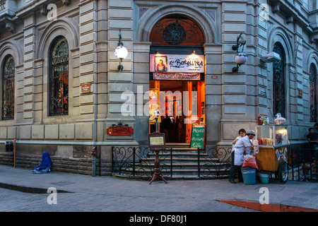 Picturesque shop, street food vendor and beggar woman on street corner in 16th century historic district of Guanajuato, - Stock Photo
