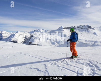 Male skier skiing in Le Grand Massif ski area looking at snowcapped mountains in the French Alps. Flaine, Rhone - Stock Photo