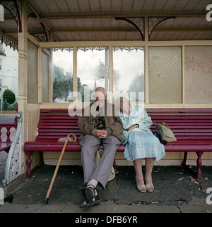 An elderly couple sleep on a sheltered bench on the promenade at the southern English resort of Southend-on-Sea, - Stock Photo