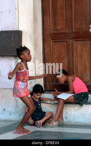 Cuban Girls infront of her House in Havanna - Stock Photo