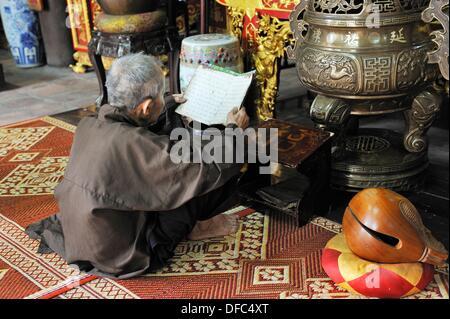 man reading, small temple adjoining One Pilar Pagoda, Hanoi, Northern Vietnam, southeast asia - Stock Photo