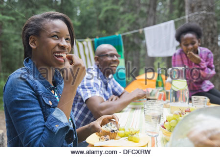 Happy girl having meal with family at campsite - Stock Photo