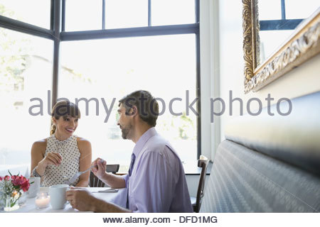 Professional couple talking at restaurant table - Stock Photo