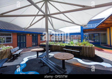 large umbrella style canopy to seats in school garden play area - Stock Photo