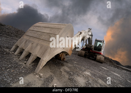 Wide angle image of an excavator in a quarry with a dramatic sky background. Focus on the shovel in the foreground. - Stock Photo