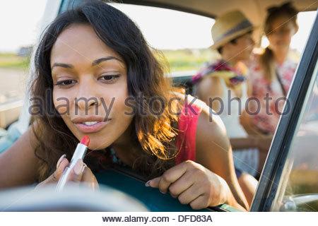 Woman applying lipstick in rear view mirror - Stock Photo