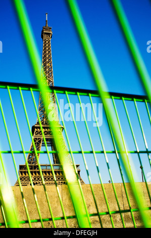 A view of the Eiffel Tower taken through an abandoned green shopping trolley. - Stock Photo