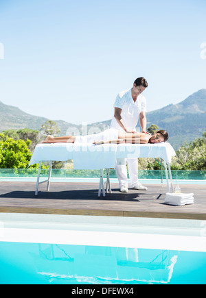 Woman receiving massage at poolside - Stock Photo
