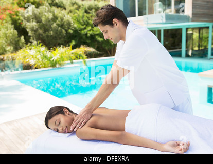 Woman receiving massage poolside at spa - Stock Photo