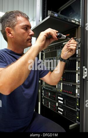 Man using screwdriver, compute cluster maintenance - Stock Photo
