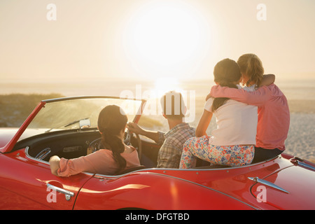 Family watching sunset over ocean from convertible on beach - Stock Photo