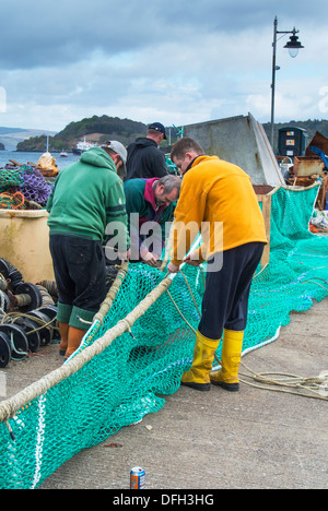 Local working fishermen repairing fishing nets on the harbour wall at Tobermory, inner hebrides, Scotland. - Stock Photo