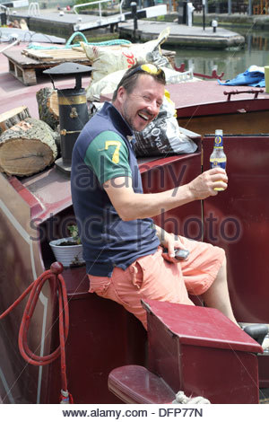 man having a beer on a canal boat at camden town lock and market in london - Stock Photo