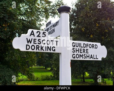 Traditional rural white English road sign on A 25 pointing towards Westcott and Dorking, Guildford Shere and Gomshall. - Stock Photo