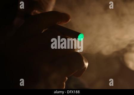 A person smoking an electronic cigarette - Stock Photo