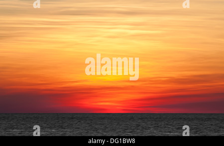 Layers of colors formed from a light layer of clouds sitting over the horizon in Key West, Florida. - Stock Photo