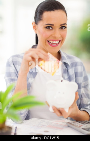 cheerful young woman putting money in piggy bank - Stock Photo