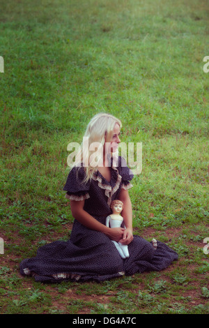 a woman in a romantic dress with an old doll on a meadow - Stock Photo