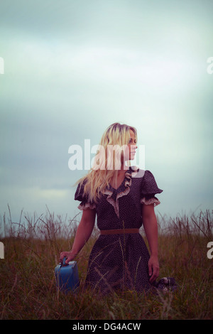 a woman in a romantic dress on a meadow with a suitcase - Stock Photo