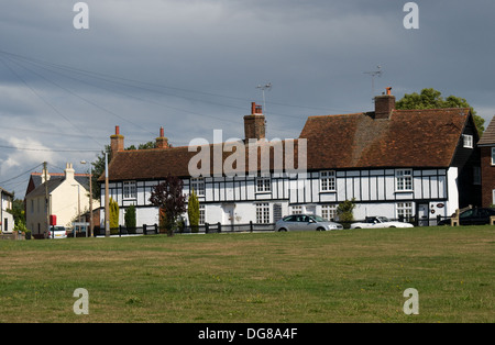 A row of wooden framed houses stand along the north eastern edge of Hurst Green in Brightlingsea, Essex - Stock Photo