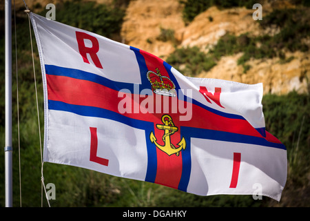 The Royal National Lifeboat (RNLI) flag flying above the beach at Bournemouth during the height of the holiday period - Stock Photo
