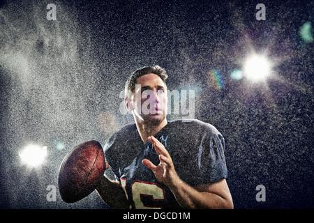 American footballer preparing to throw ball - Stock Photo