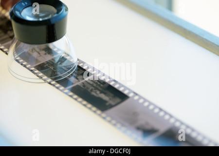 Strip of black and white negative film on lightbox - Stock Photo