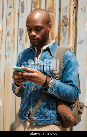 Portrait of young man using smartphone - Stock Photo