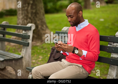 Young man sitting on park bench using mobile phone - Stock Photo