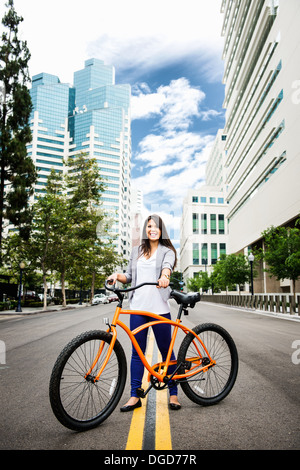 Young woman standing road with bicycle in city, smiling - Stock Photo