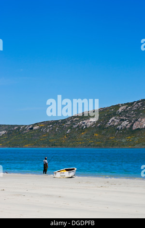 A lone fisherman and boat on the Langerbaan lagoon - Stock Photo