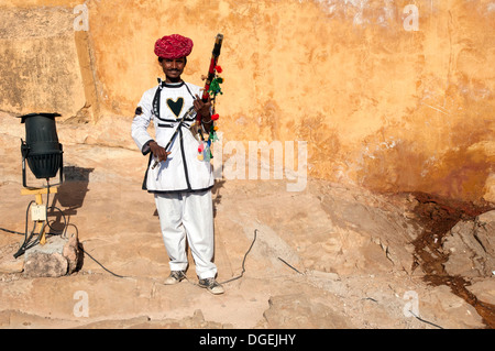 Rajasthani man posing with traditional instrument outside Amer Fort, Jaipur, India - Stock Photo