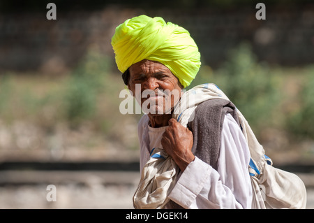 Rajasthani man in yellow turban carries a sack in Ranthambore, India. - Stock Photo