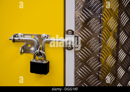 Padlock on a yellow metal door - Stock Photo
