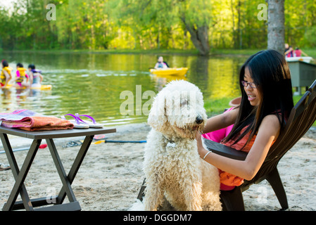 Girl sitting on chair by lake with dog - Stock Photo