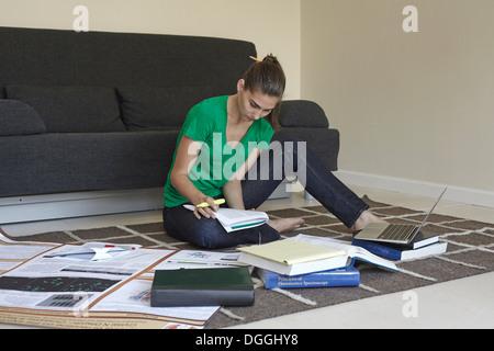 Mid adult woman sitting on floor studying - Stock Photo