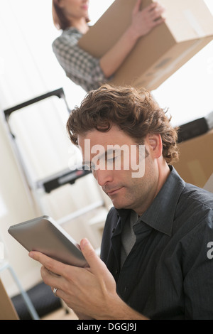 Man looking at digital tablet whilst moving home - Stock Photo