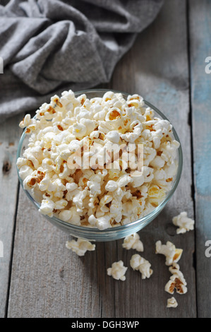 Popcorn in glass bowl over wooden background - Stock Photo