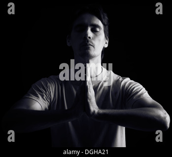 Portrait of a man meditating with his hands clasped together isolated on black background - Stock Photo