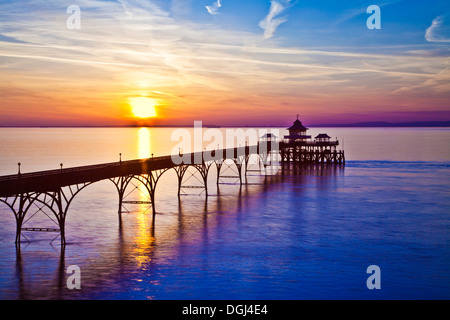 The sun sets over the Bristol Channel behind the pier at Clevedon in Somerset. - Stock Photo