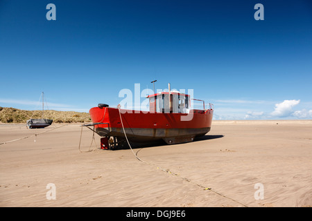 A red fishing boat beached at Barmouth. - Stock Photo