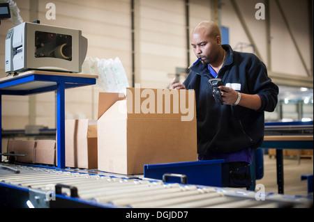 Male warehouse worker checking cardboard box - Stock Photo